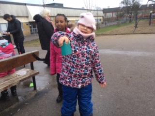 Barn håller upp föremål och ser stolt ut.