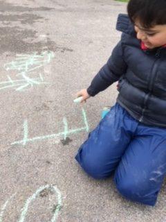 Barn skriver bokstav med gatukrita på vägen.