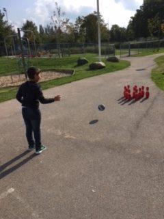 Barn spelar bowling utomhus.