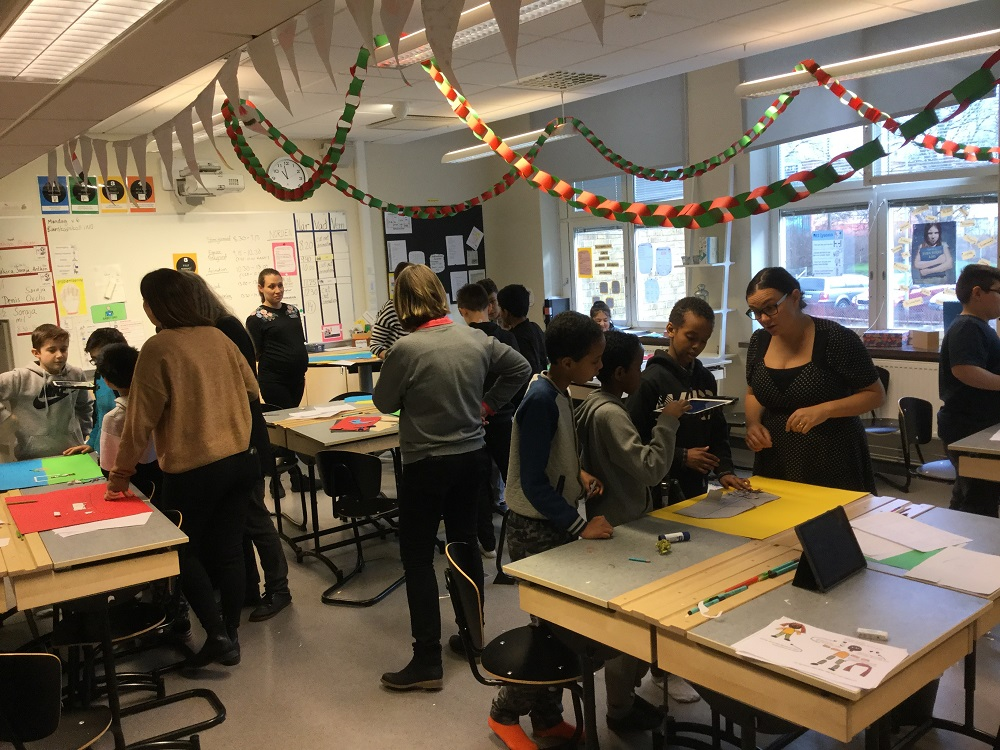 Elever i klassrum jobbar vid skrivbord.