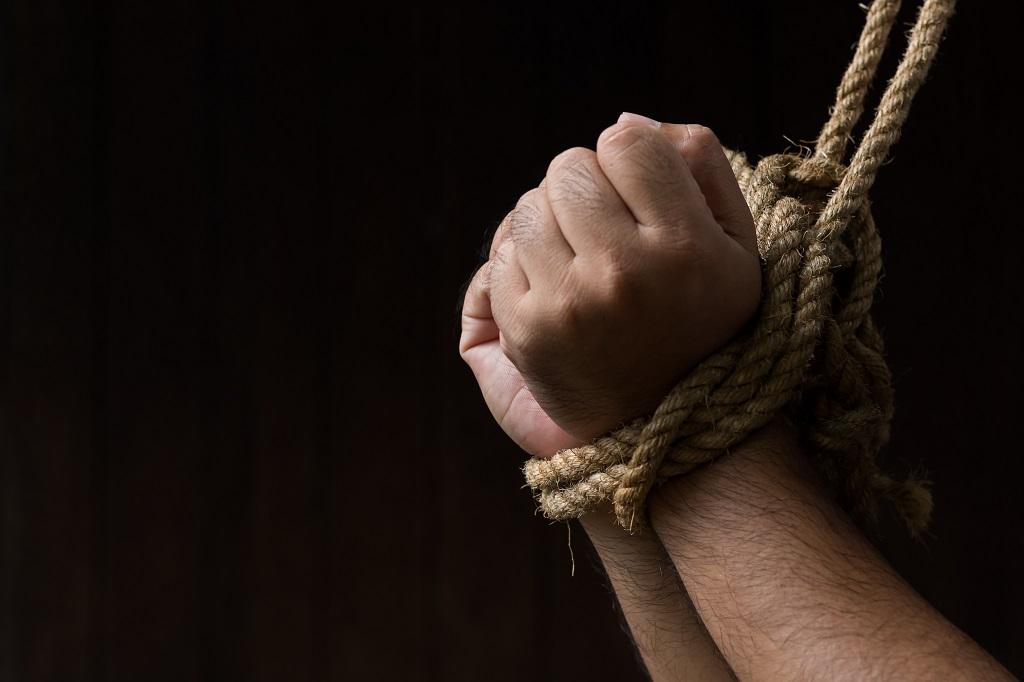 Händer knutna med rep.