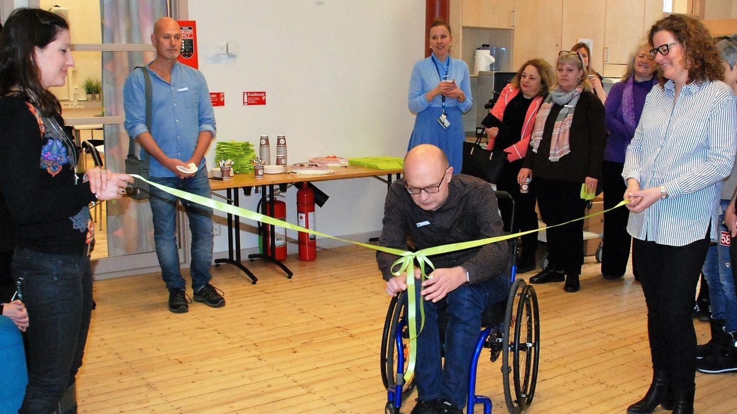 Man i rullstol klipper invigningsband.