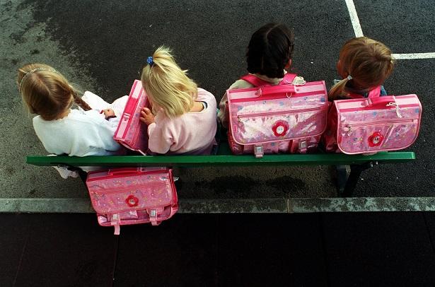 Fyra barn med rosa ryggsäckar sitter på bänk.