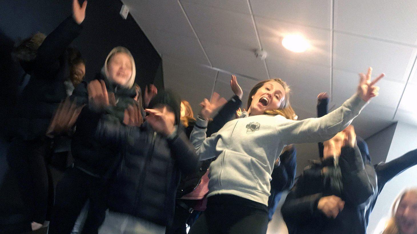 Elever och pedagog dansar och hoppar.