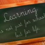 Grön tavla där det står citat om lärande.