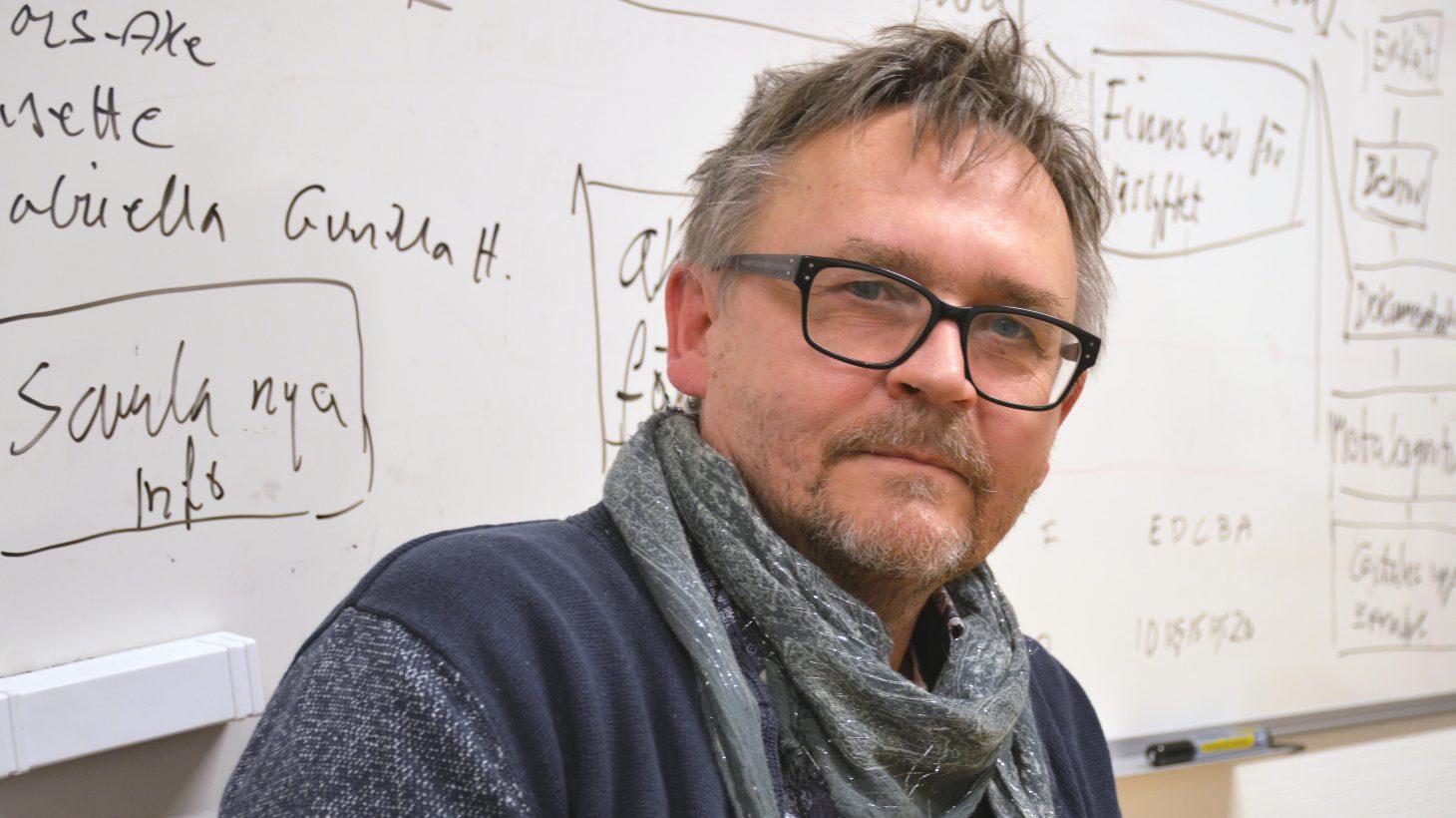 Thomas framför whiteboard full av anteckningar.