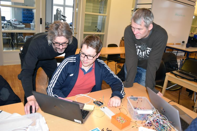 Tre män tittar in i dator, bredvid dem ligger fullt av kopplingar och sladdar.