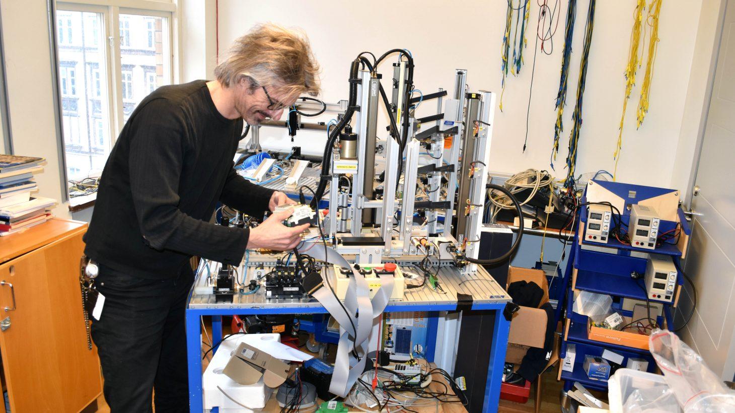 Tekniklärare kopplar i rum fullt av teknikmaterial.