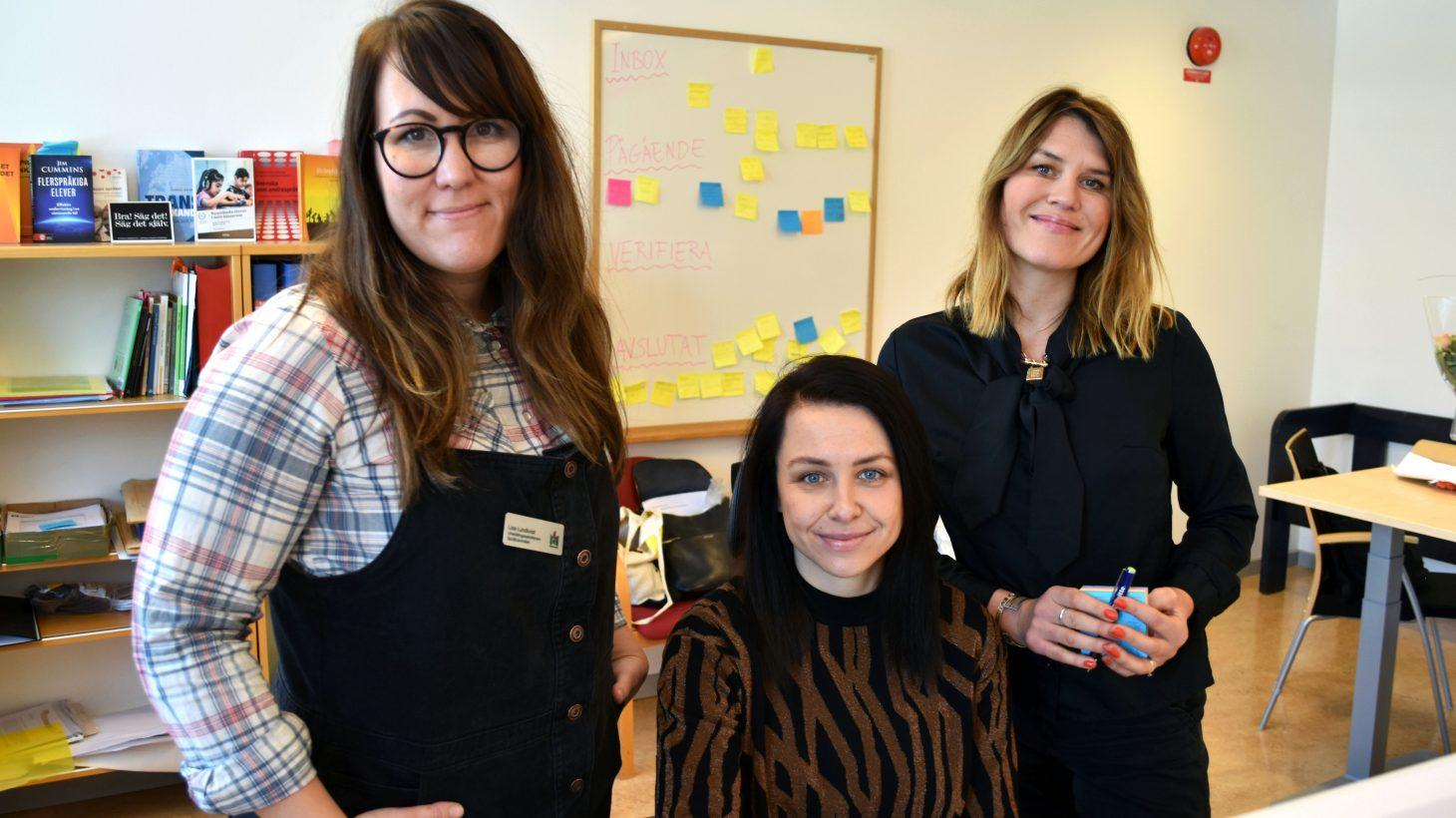 Tre kvinnor vid skrivbord.