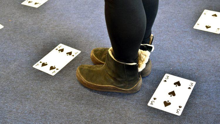 Ett par fötter står på golvet där det ligger spelkort utlagda.