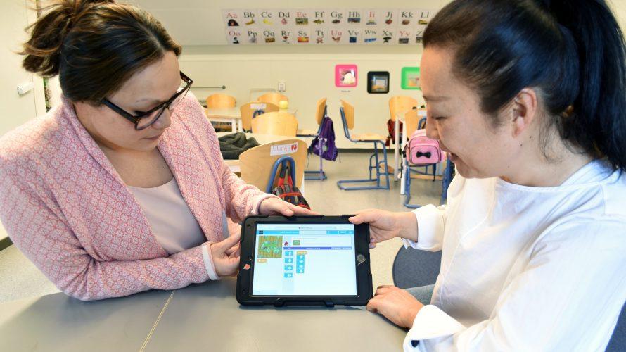 Två pedagoger håller upp läsplatta.