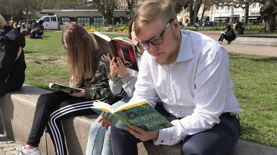 Skolbibliotekarie och elever sitter och läser på stenbänk i Malmö.