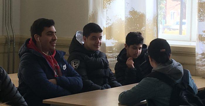 Fyra elever sitter runt bord.