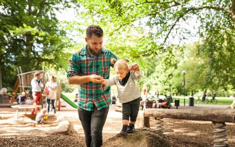 Man håller barn som balanserar på en stock i händerna.