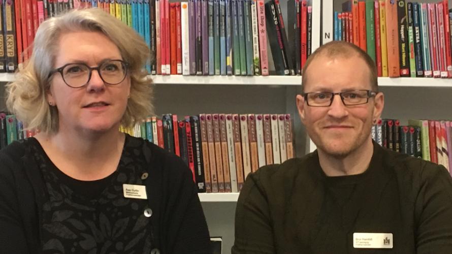 Bibliotekarie och IKT-pedagog framför fulla bokhyllor.