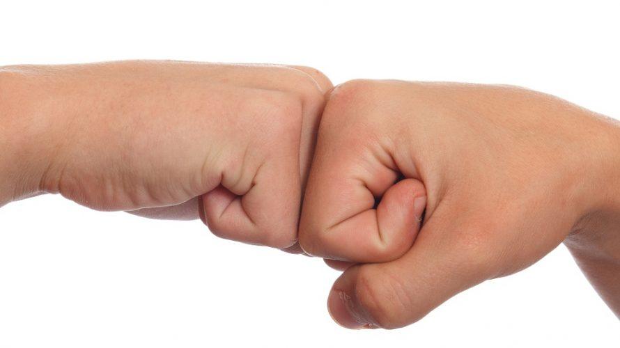 Två knutna nävar möter varandra.