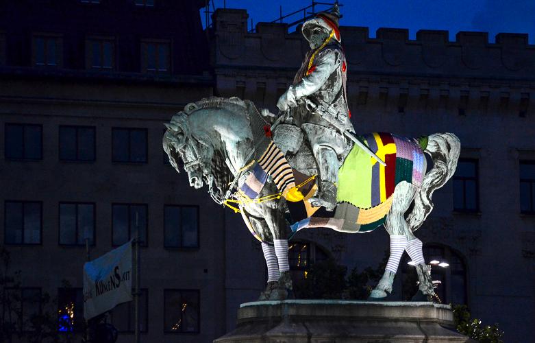 Staty av man till häst klädd i stickade halsdukar.