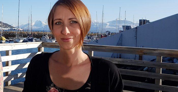 Kvinna med hamn och berg i bakgrunden.