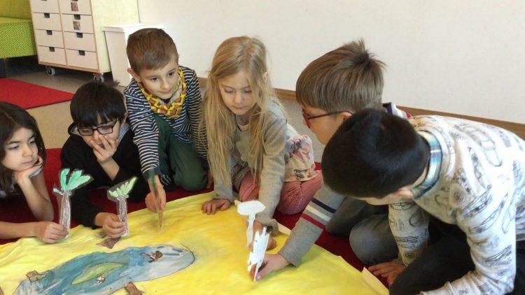 Barn sitter vid stor teckning och leker med karaktärerna.