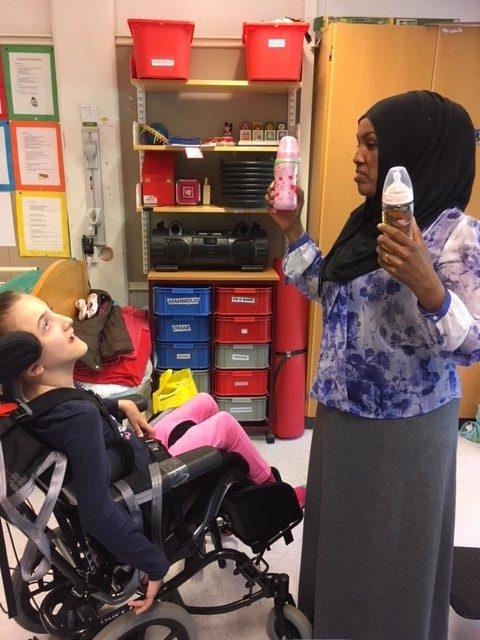 Elev i rullstol tittar på pedagog som visar upp flaskor.