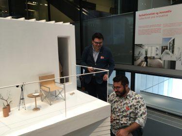 Två män vid 3dmodell av byggnad och möbler.