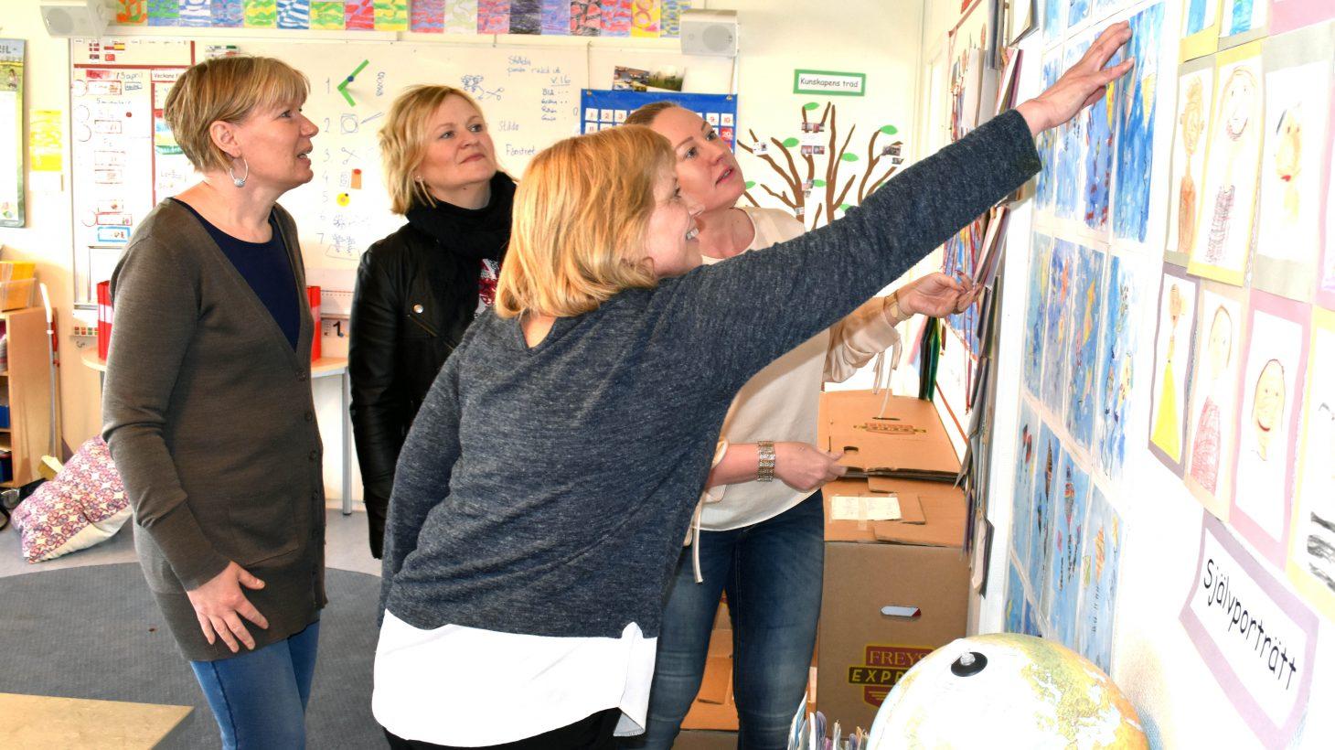 Fyra pedagoger tittar och sätter upp teckningar på vägg.
