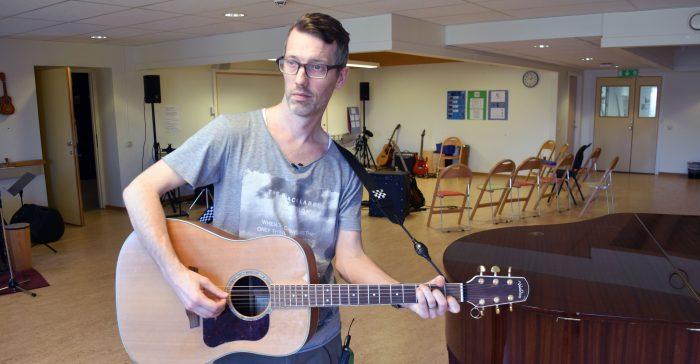 Man med gitarr i musiksal.