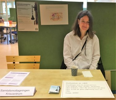 Kvinna från Samtalsmottagningen sitter bakom sitt utställarbord.