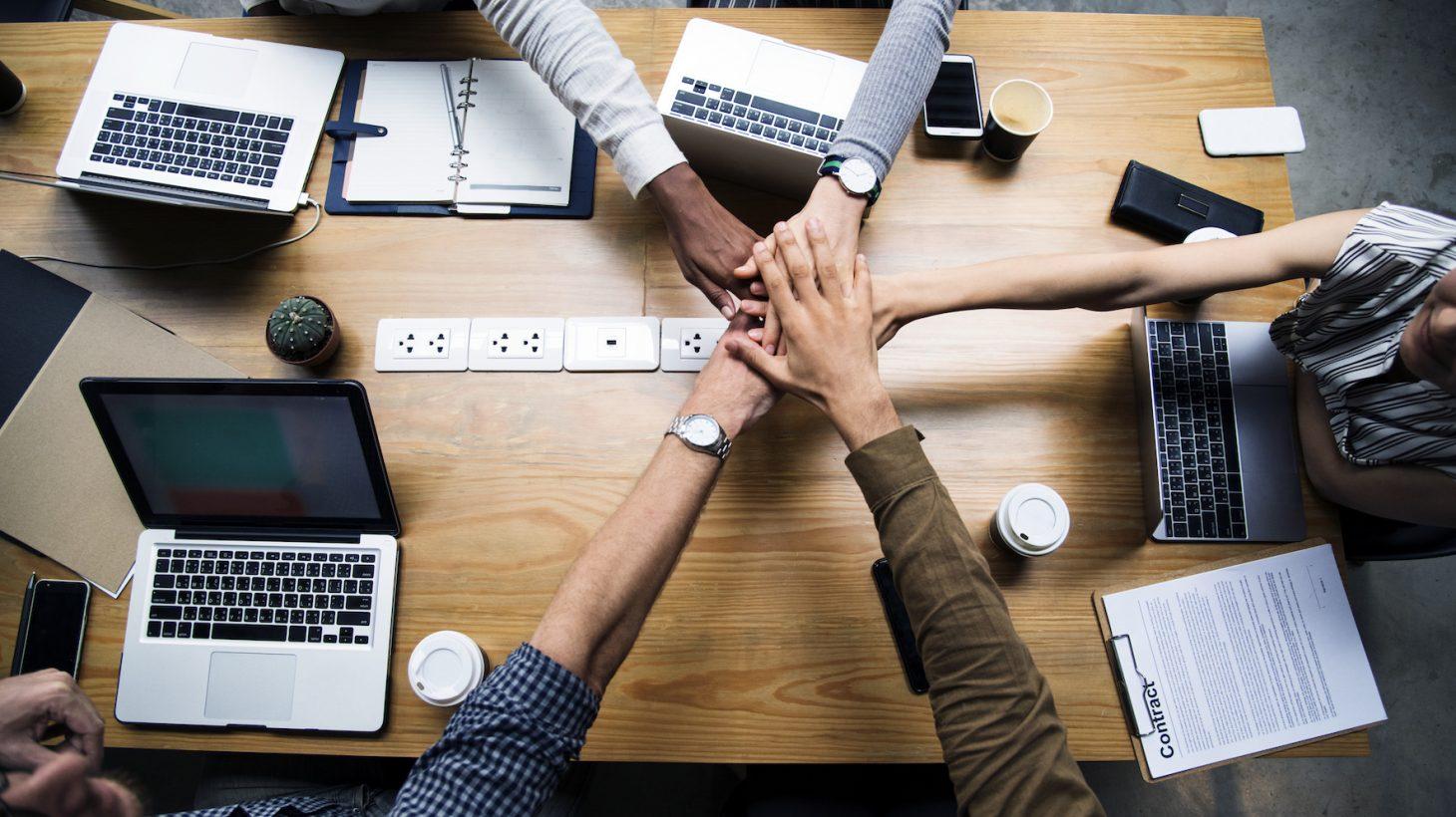 Fem händer möts i mitten över ett bord fyllt av datorer.