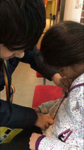 Ett barn hjälper ett annat att knäppa blixtlåset.