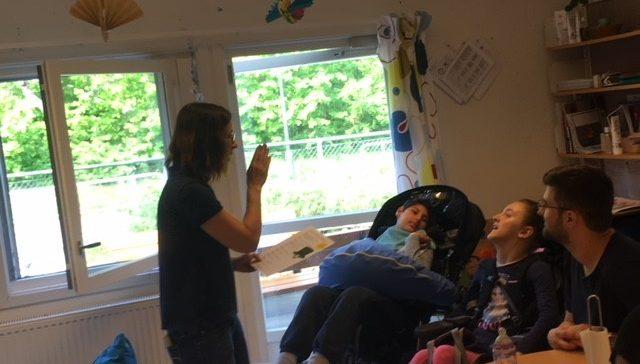 Elever i rullstol tittar på pedagog som berättar.
