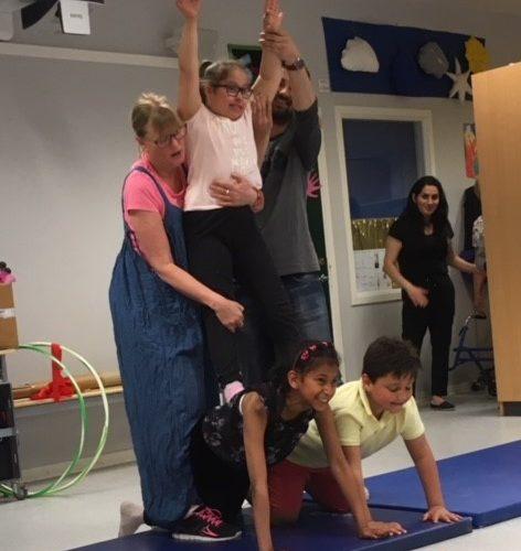 Barn skapar pyramid genom akrobatik.