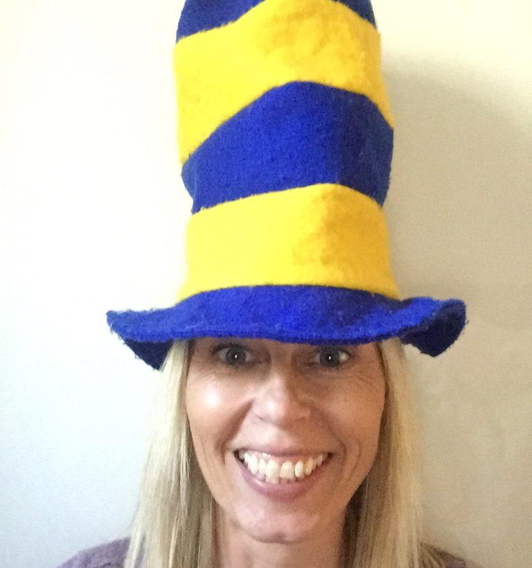 Kvinna med hög gul och blå hatt på huvudet.