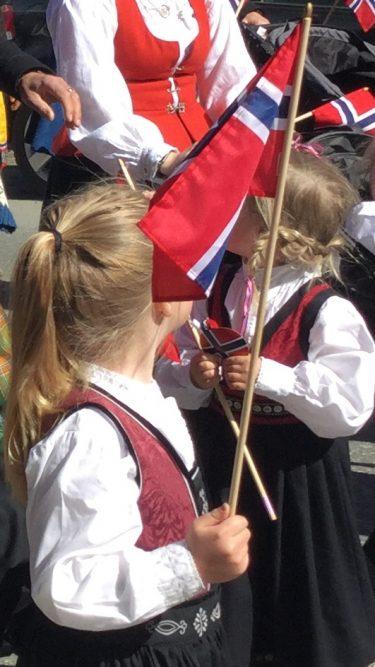 Två små barn i norska folkdräkter viftar med norsk flagga.