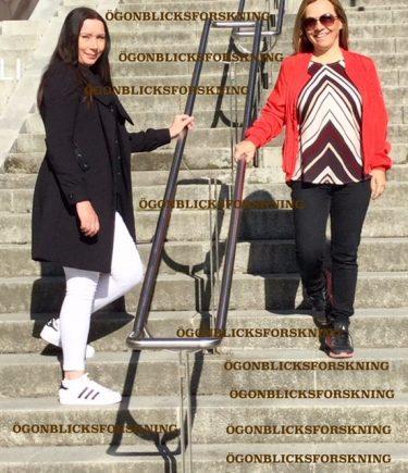 Två kvinnor står i en trappa där en går upp och en går ner.