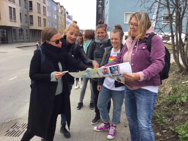 Grupp av personer tittar och pekar på karta.