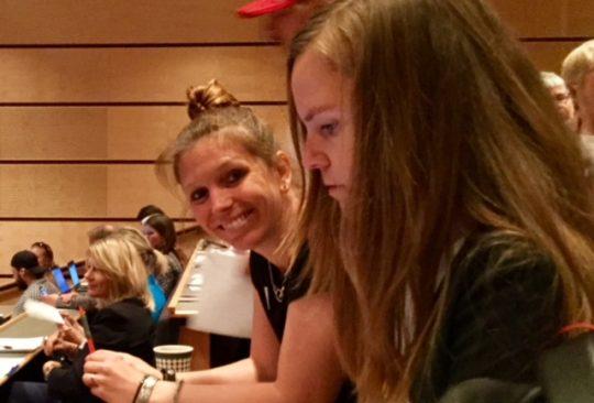 Två kvinnor sitter på åhörarläktare.