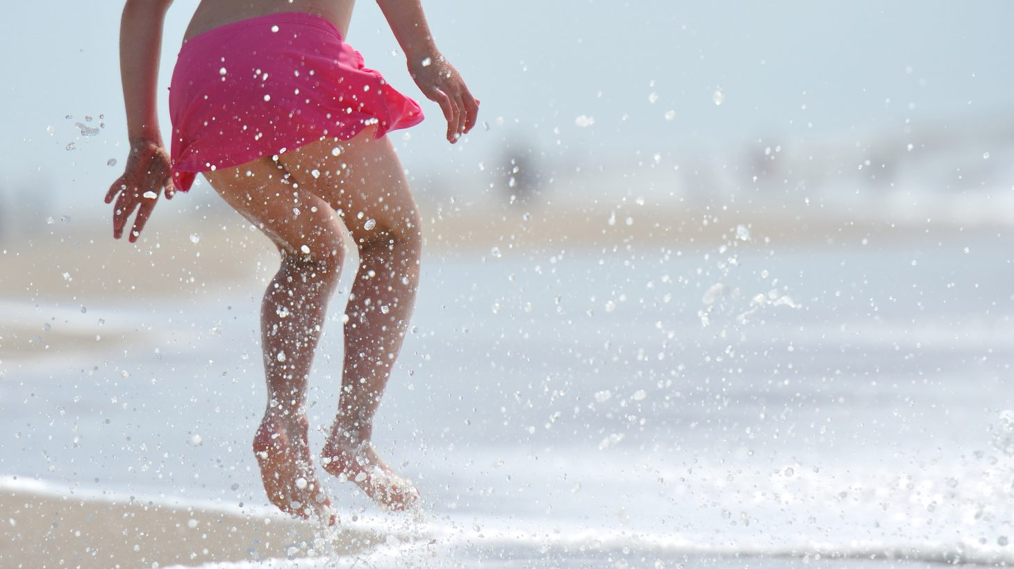 Flicka hoppar på stranden vid vattenkanten.