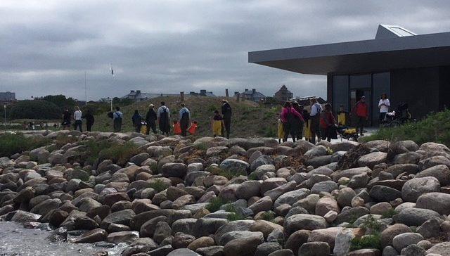 Elever i vadarbyxor går vid havsbryn.