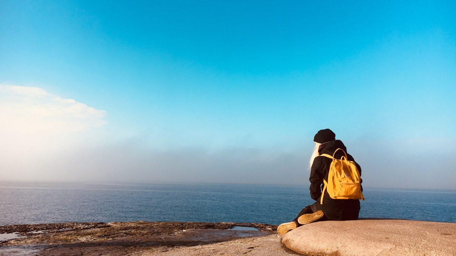 Kvinna sitter på sten och blickar ut över hav.