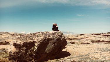 Kvinna sitter på jättestor sten.