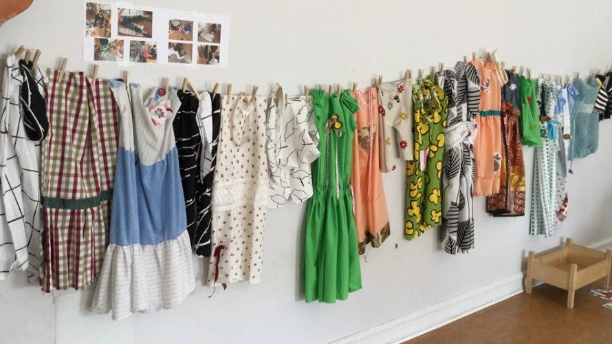 Barnens kläder som de själva sytt hänger på rad på en vägg