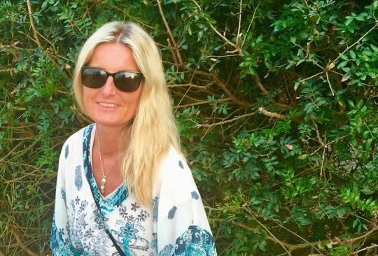 Kvinna med solglasögon vid träd.