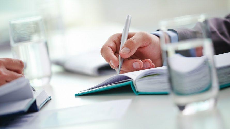 Händer som skriver på ett block.