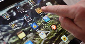 Finger som pekar på app på läsplatta.