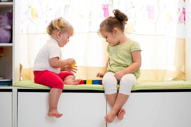Två barn sitter och leker på en bänk inomhus