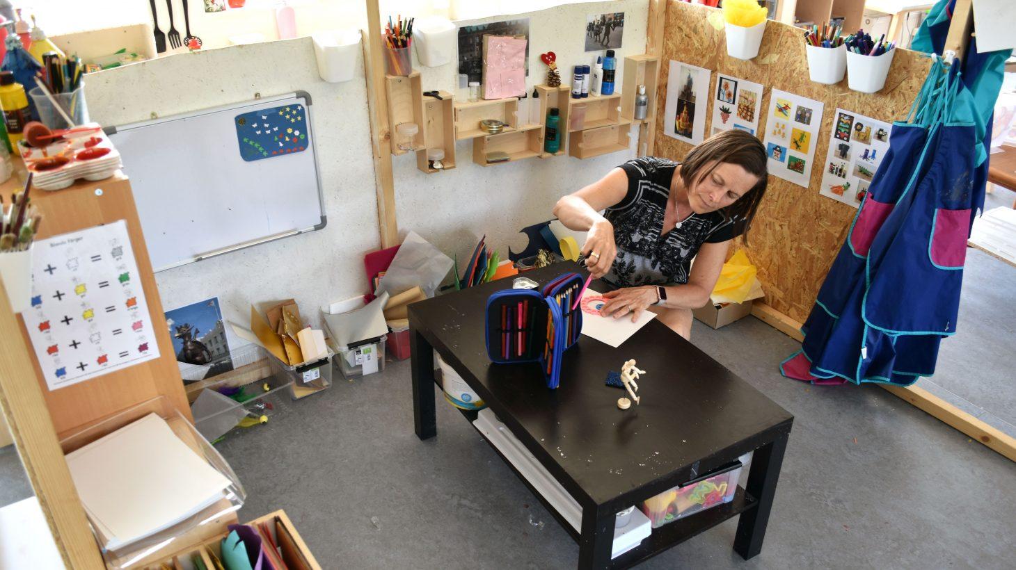 Anette Freij sitter vid lågt bord och tecknar.
