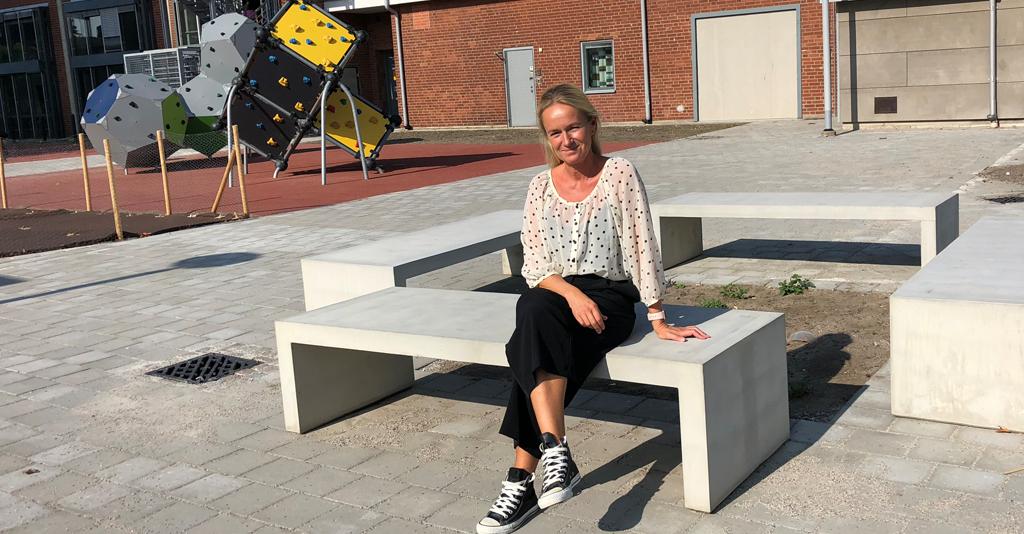 Martina Soomro sitter på bänk utanför skola.