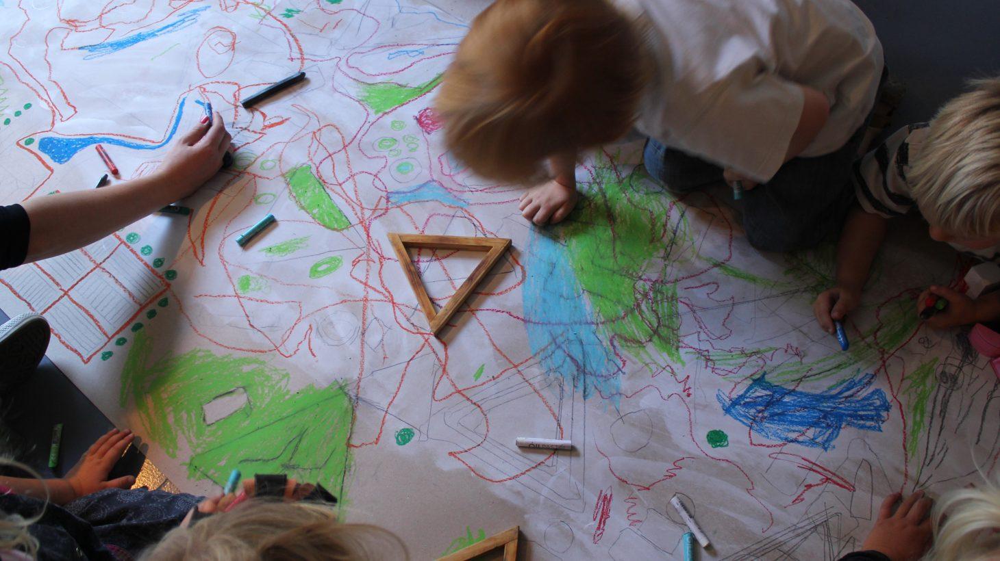Barm målar på stort papper på golvet.