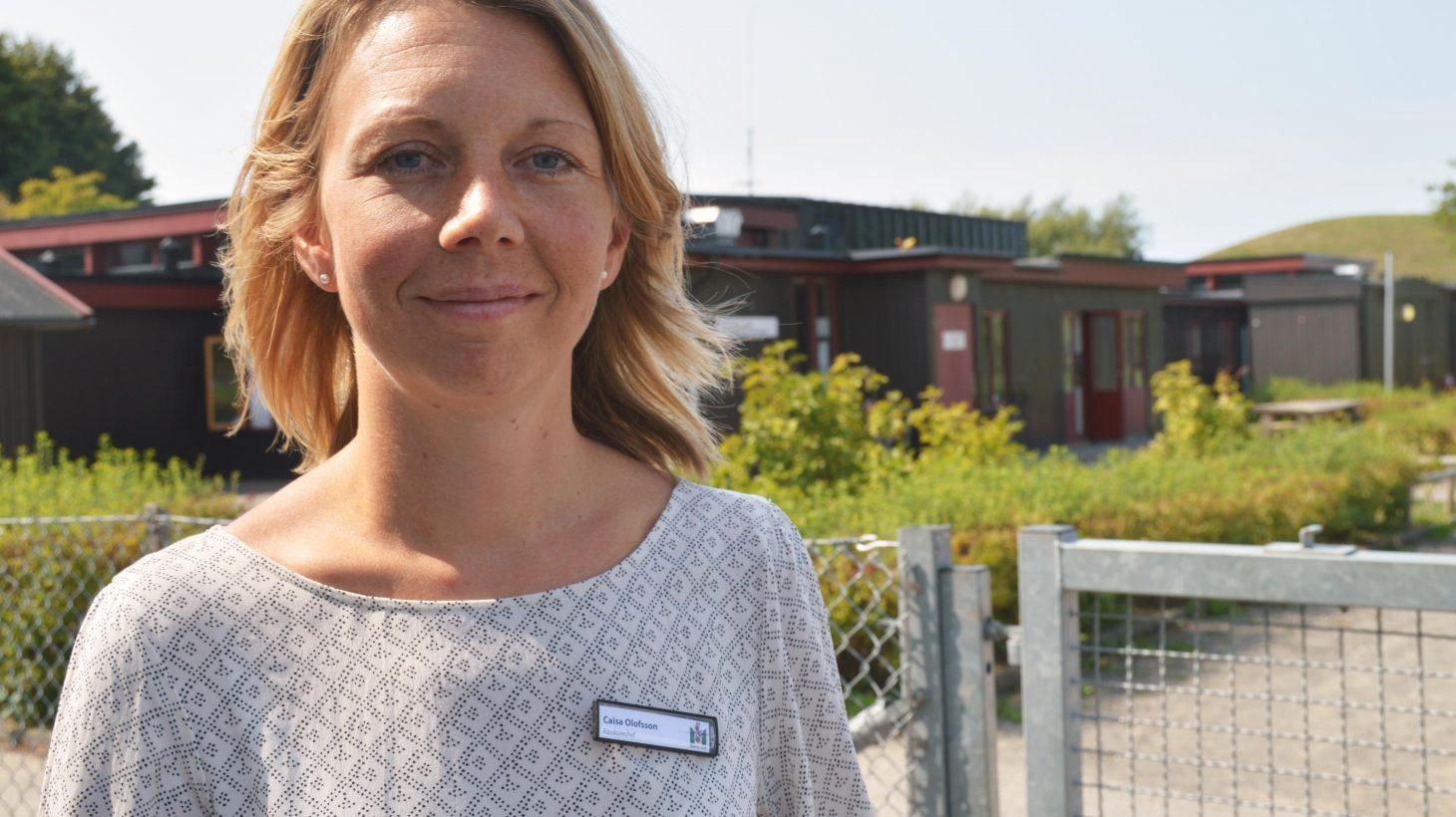 Caisa Olofsson framför den byggnad som klarade sig undan branden.